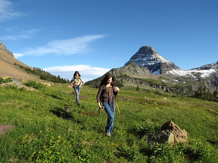 M and E walk down a grassy slope near Hidden Lake