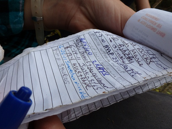 Signing the geocache log book.